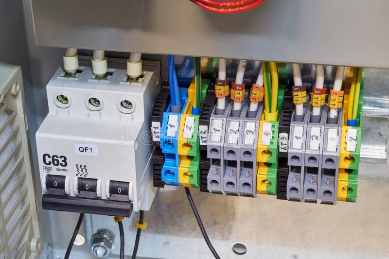 Modular circuit breaker and a number of terminals in the electrical Cabinet. Electrical wires or cables are connected to the switch and terminals. Reliable and royalty free stock photo