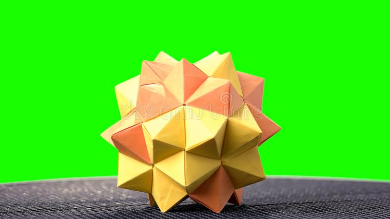 Modular origami model on green background. 3D yellow paper figure. Creativity and art royalty free stock photos