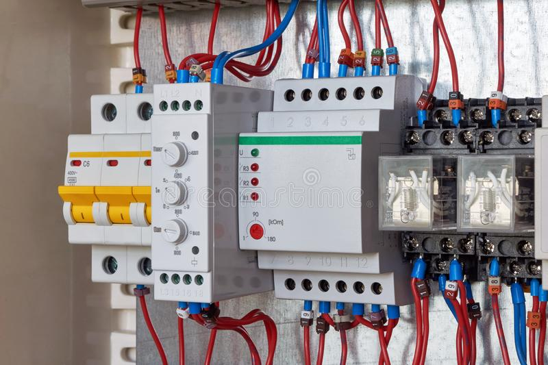 Circuit breaker, phase control relay, level control relay, intermediate relays in electrical Cabin. Modular three-phase circuit breaker, phase control relay with stock photos