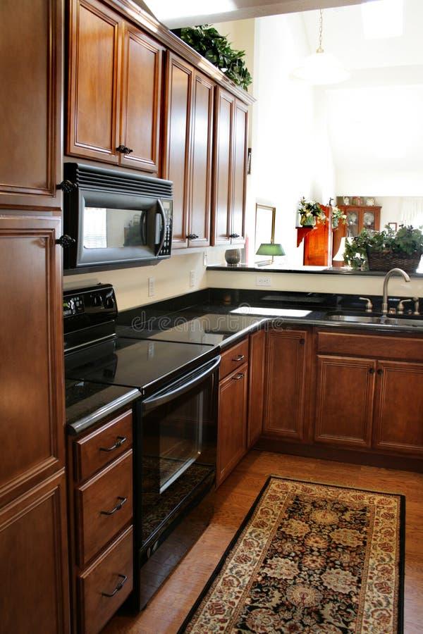 Modules en bois de cuisine noirs et poêle inoxidable images stock