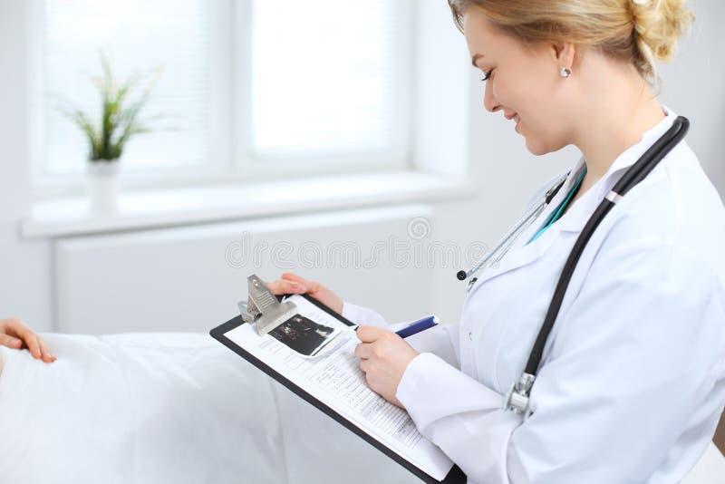 Modulo di domanda femminile della tenuta di medico mentre consultando paziente immagini stock libere da diritti