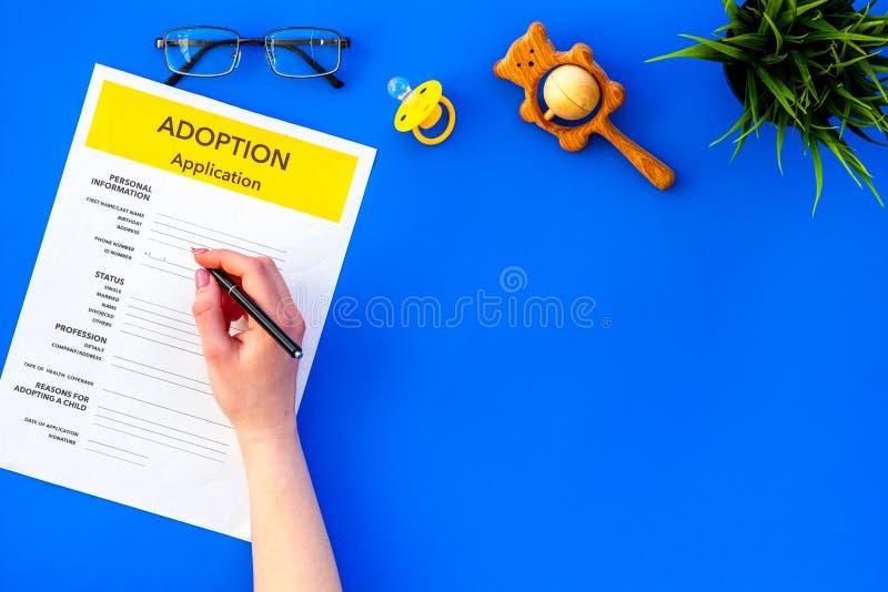 Modulo di domanda per adottare bambino su derisione blu di vista superiore del fondo su fotografia stock libera da diritti