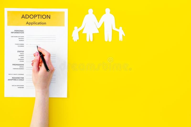Modulo di domanda per adottare bambino su derisione gialla di vista superiore del fondo su fotografie stock