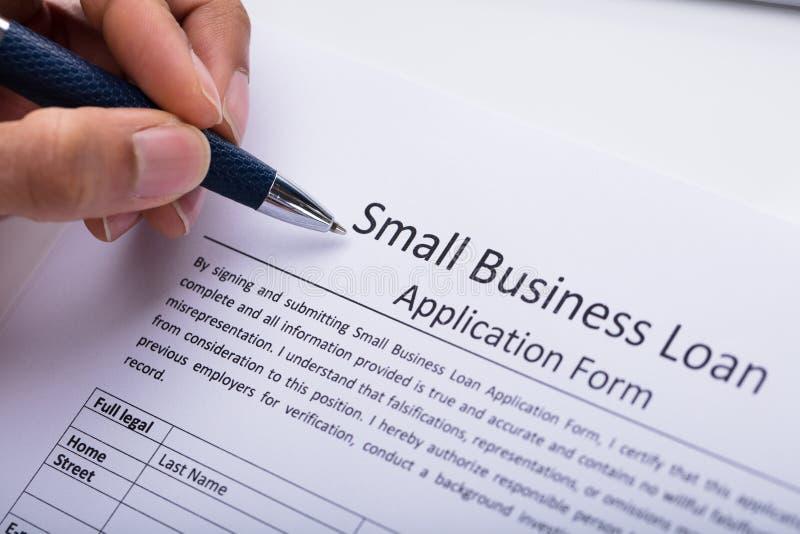 Modulo di domanda di prestito di Filling Small Business della persona di affari fotografie stock