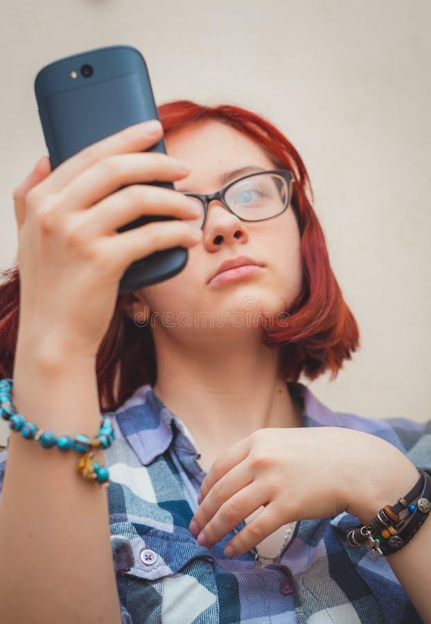 Mody ładna młoda dziewczyna robi selfie portretowi na smartphone obrazy royalty free