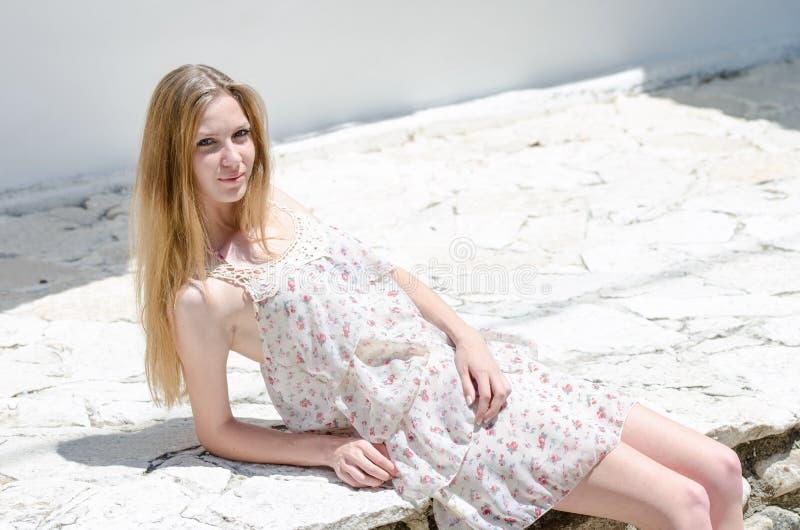 Mody blondynka jest ubranym kwiat sukni pozę pod jaskrawym słońcem obraz stock