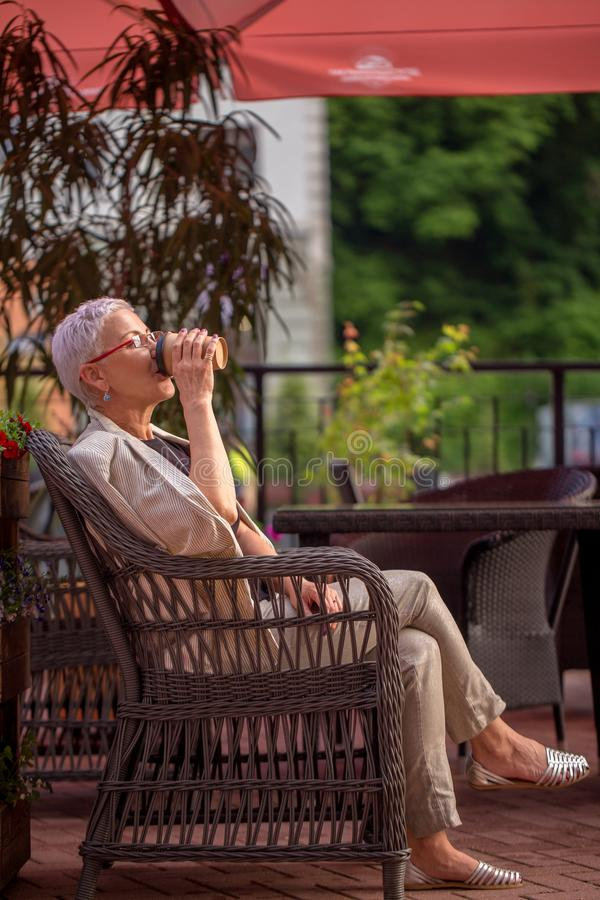 Mody dojrzała kobieta pije kawę w karle zdjęcie royalty free