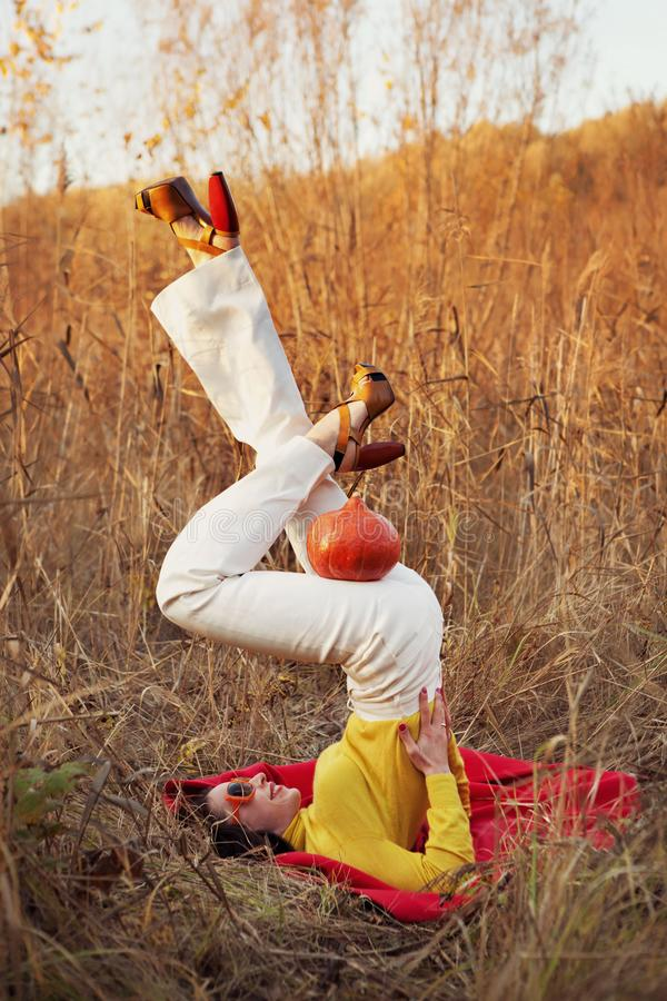 Mody dziewczyna z banią robi ramię stojaka ćwiczeniu pieszo, asana Viparita Karany, do góry nogami foki poza obrazy stock