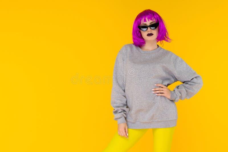 Mody dziewczyny portret na żółtym tle Szalona stylowa młoda kobieta w różowej peruce fotografia stock