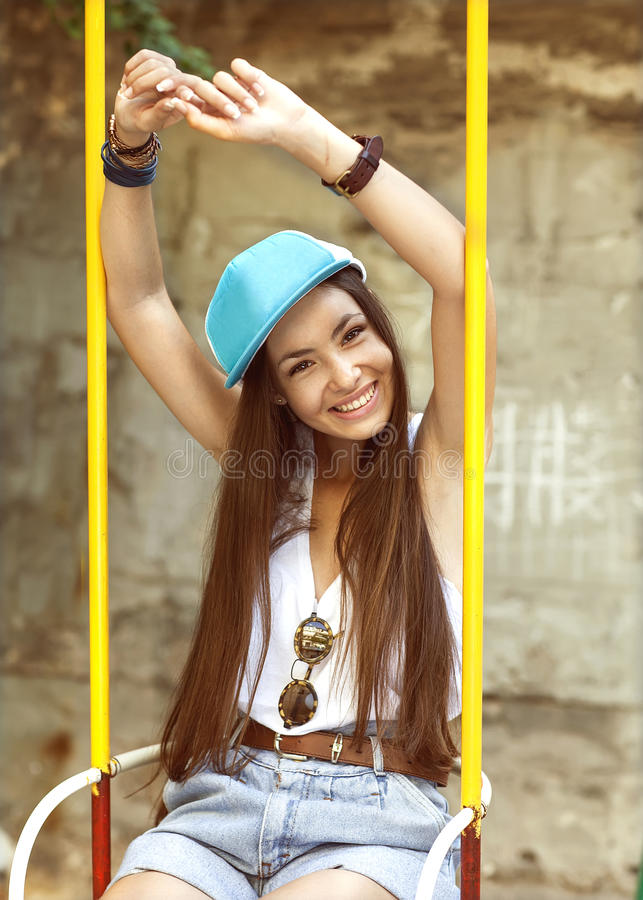 Mody dziewczyny przejażdżka na huśtawce Modnisia styl zdjęcia stock