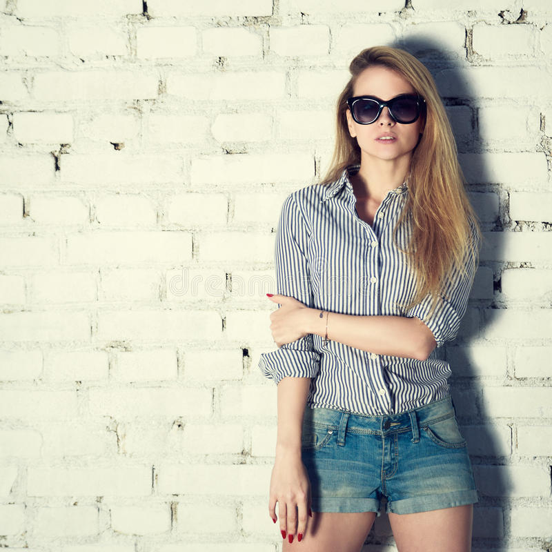 Mody fotografia modniś kobieta przy ściana z cegieł zdjęcie royalty free