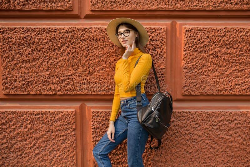 Mody kobieta stoi blisko pomarańczowej ściany zdjęcie stock