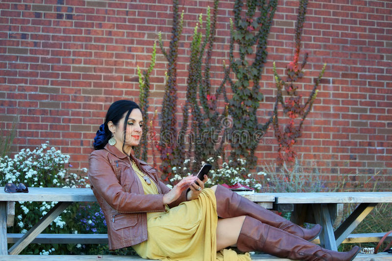 Mody kobieta używa mądrze telefon zdjęcia stock