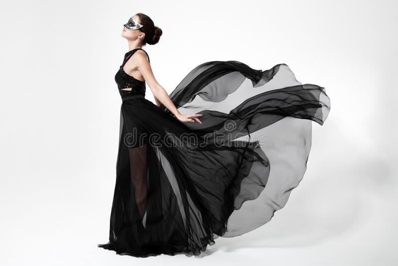Mody kobieta w trzepotliwej czerni sukni Biały tło obraz royalty free