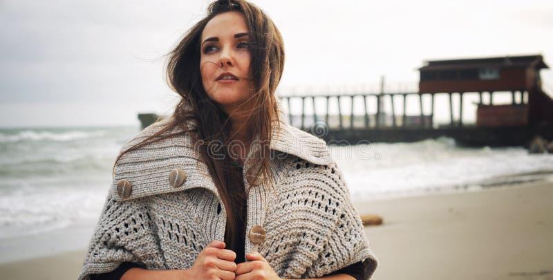 Mody kobiety portret przeciw molu na dennej plaży, jesieni plenerowa moda zdjęcia royalty free