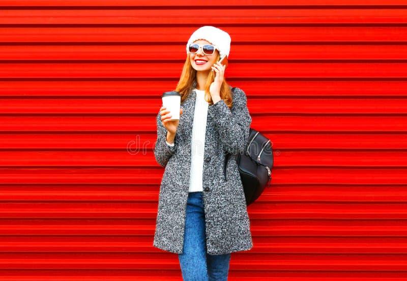Mody kobiety uśmiechnięte rozmowy na smartphone trzymają filiżankę na czerwieni zdjęcia royalty free