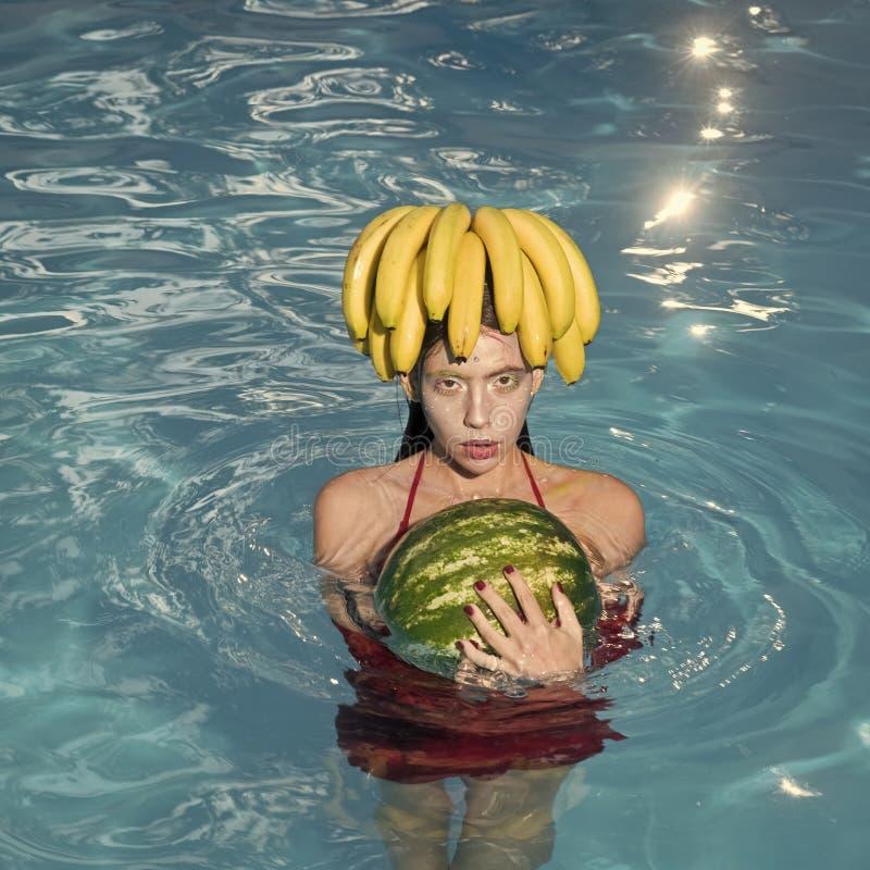 Mody kobiety wzorcowy pozować Dziewczyna na plażowym chwyta arbuzie, bananie w błękitnym basenie i Tropikalnej owoc dieta Lato zdjęcia stock