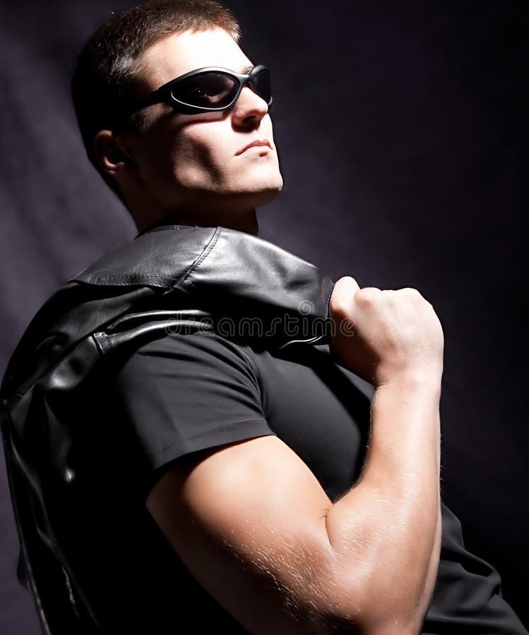 Mody męscy whit okulary przeciwsłoneczne trzymają czarny kurtkę zdjęcie royalty free