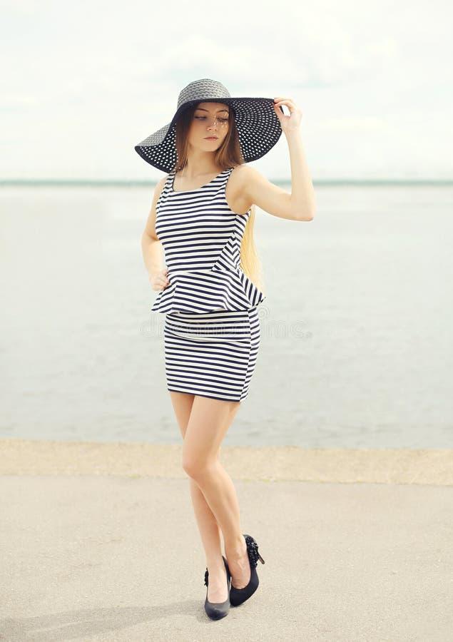 Mody młoda kobieta jest ubranym pasiastą suknię czarnego słomianego kapelusz i obrazy stock