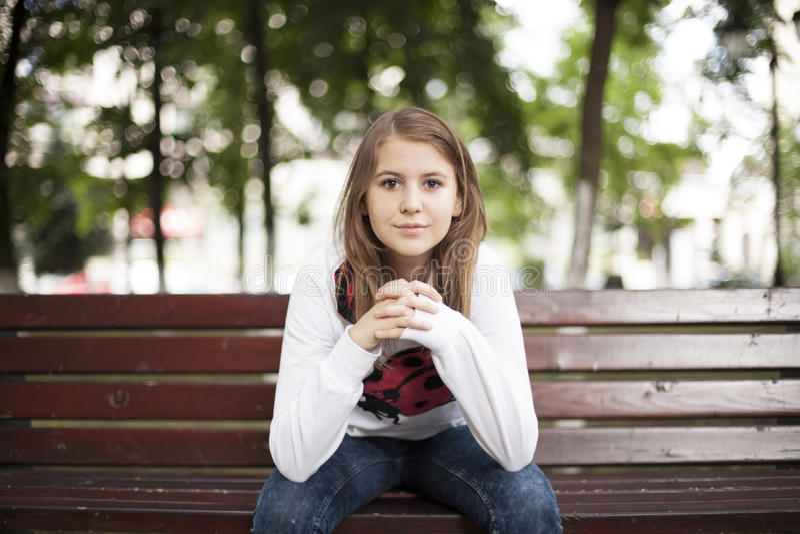 Mody młoda kobieta ono uśmiecha się na ławce obrazy royalty free
