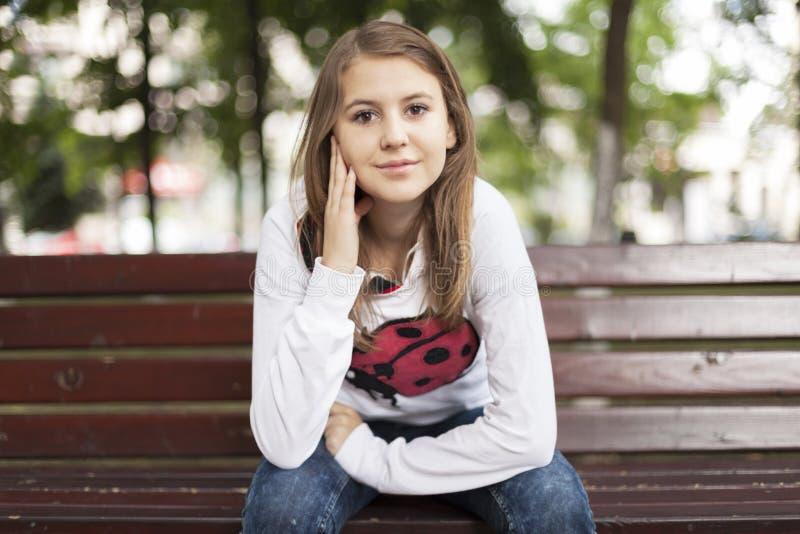 Mody młoda kobieta ono uśmiecha się na ławce zdjęcia stock