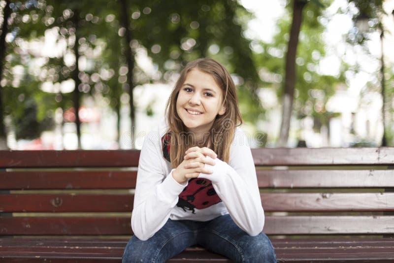 Mody młoda kobieta ono uśmiecha się na ławce obrazy stock