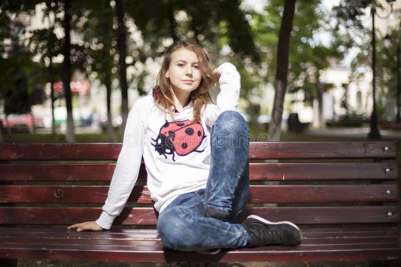 Mody młoda kobieta ono uśmiecha się na ławce zdjęcie royalty free