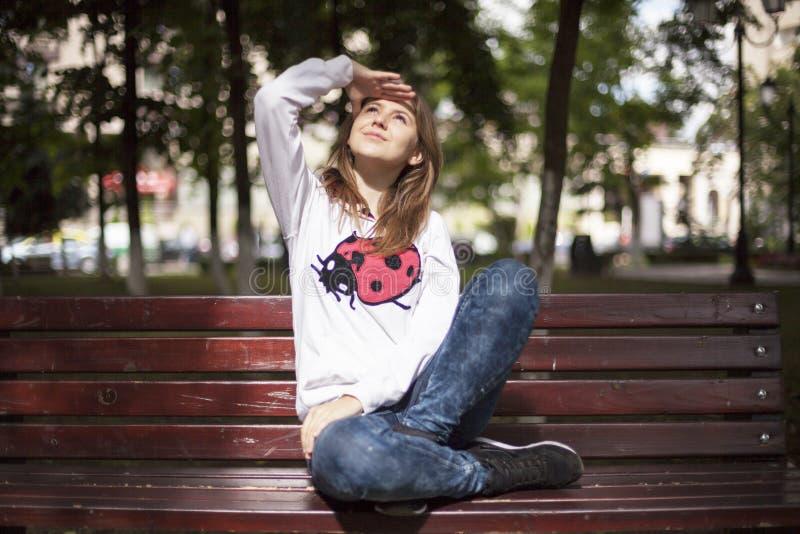 Mody młoda kobieta ono uśmiecha się na ławce fotografia royalty free