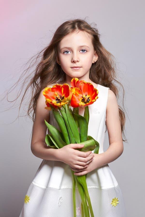 Mody miedzianowłosa dziewczyna z tulipanami w rękach Pracowniana fotografia na światło coloured tle Urodziny, wakacje, macierzyst obraz royalty free