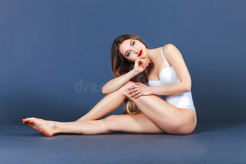 mody modela target1721_0_ studio Dysponowana kobieta w swimsuit Piękna i zdrowa kobieta pozuje nad błękitnym tłem fotografia royalty free