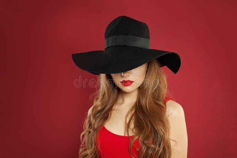 Mody piękna portret doskonalić wzorcowa kobieta w czarnym kapeluszu na czerwonym tle obraz stock