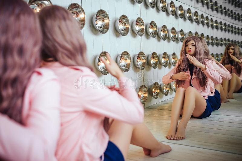 Mody pokraka Splendor syntetyczna dziewczyna, sfałszowana lala z pustym spojrzeniem i długi lily włosy, siedzimy w studiu eleganc zdjęcie royalty free