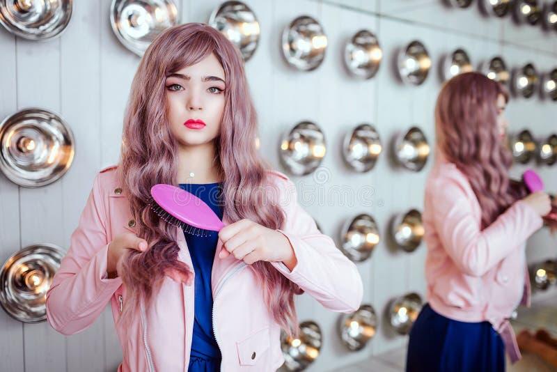 Mody pokraka Splendor syntetyczna dziewczyna, sfałszowana lala z pustym spojrzeniem i długi lily włosy, trzymamy różowego hairbru obraz royalty free