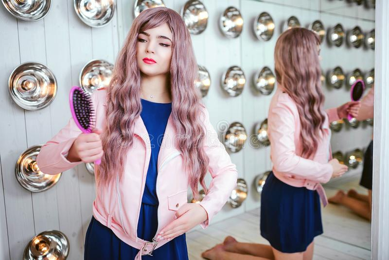 Mody pokraka Splendor syntetyczna dziewczyna, sfałszowana lala z pustym spojrzeniem i długi lily włosy, trzymamy różowego hairbru obrazy stock