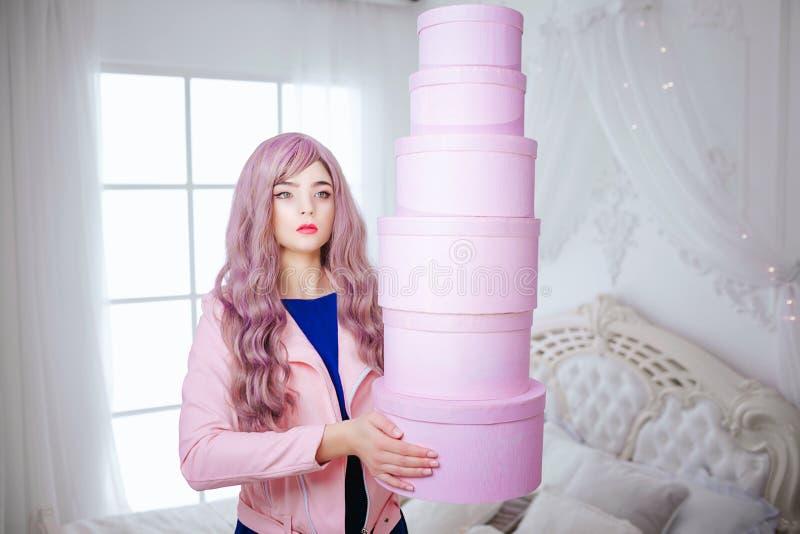 Mody pokraka Splendor syntetyczna dziewczyna, sfałszowana lala z pustym spojrzeniem i długi lily włosy, trzymamy różowych pudełka obrazy stock