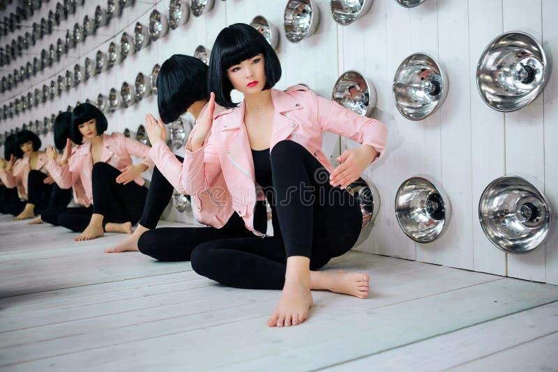 Mody pokraka Splendor syntetyczna dziewczyna, sfałszowana lala z pustym spojrzeniem i krótki czarni włosy, siedzimy w studiu eleg obrazy royalty free