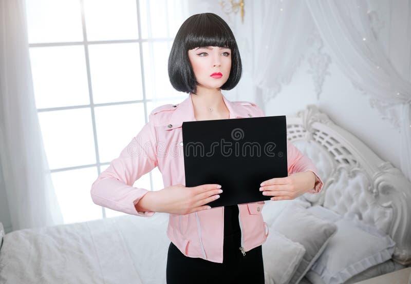 Mody pokraka tu twój tekst Splendor syntetyczna dziewczyna, sfałszowana lala z krótkim czarni włosy patrzeje oddaloną i trzyma pu zdjęcia stock