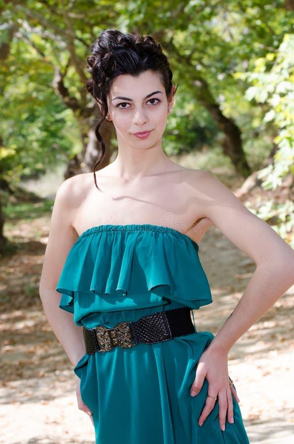 Mody szczupła kobieta jest ubranym zieleni smokingową pozycję po środku drogi gruntowej fotografia royalty free