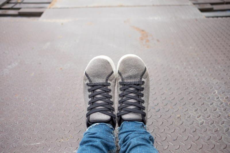 Mody tła noga jest ubranym szarego przypadkowego but i cajg z kopii przestrzenią kobieta fotografia stock