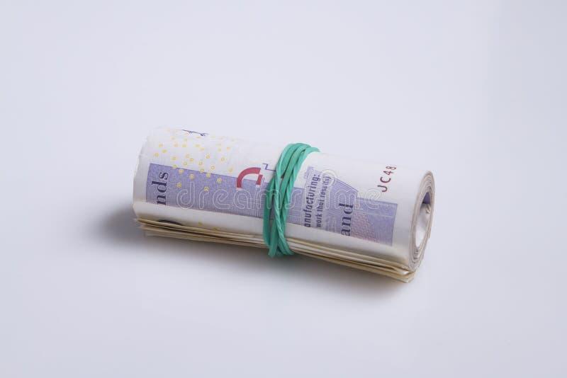 Moeda britânica O rolo de vinte notas da libra guardou pelo elástico fotografia de stock
