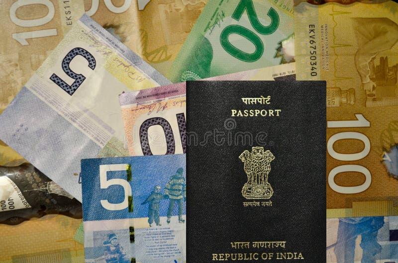 Moeda canadense da denominação 5, 10, 20, 100 com passaporte indiano foto de stock royalty free