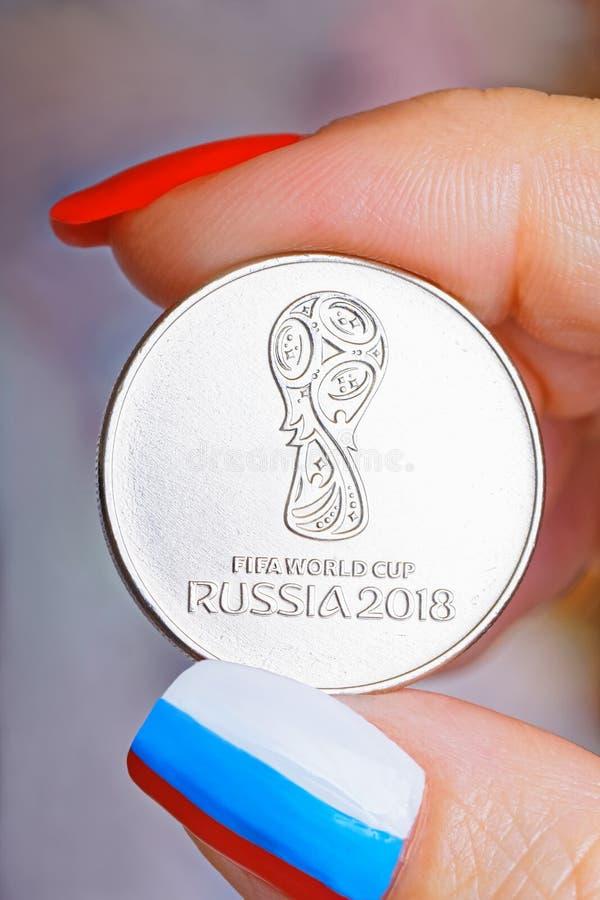 Moeda comemorativa em honra do campeonato do mundo na mão do ` s das mulheres Os pregos do dedo são pintados na cor da bandeira imagem de stock royalty free