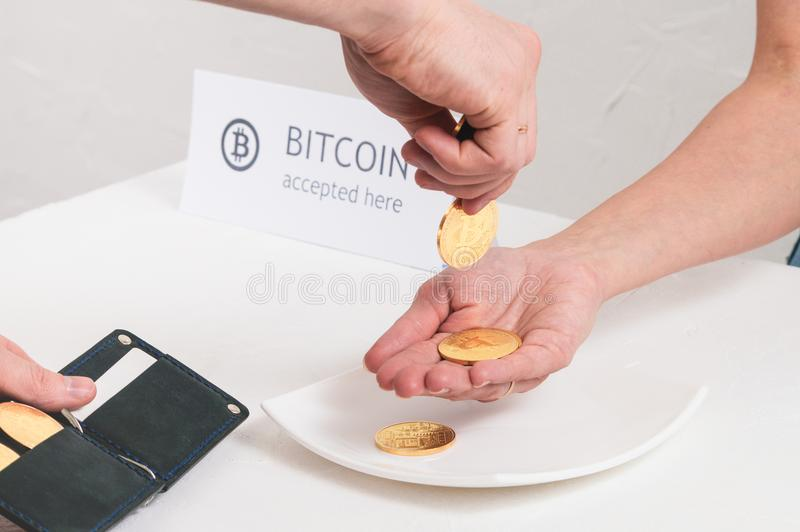 Moeda cripto do pagamento na loja: men& x27; as mãos de s puseram o bitcoin das moedas do metal na palma fêmea fotos de stock