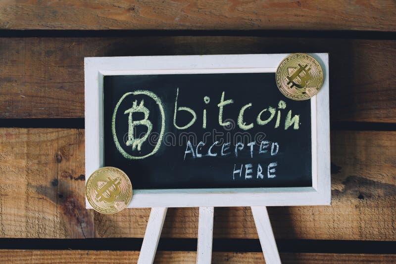 A moeda cVirtual virtual Bitcoin aceitou assina aqui sobre o fundo de madeira com bitcoins reais no canto fotografia de stock