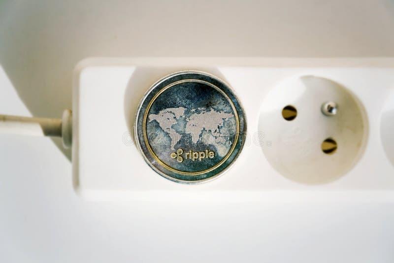 Moeda da ondinha que encontra-se no cabo de extensão da tira do poder com soquete, consumo de energia do cryptocurrency e conceit imagem de stock