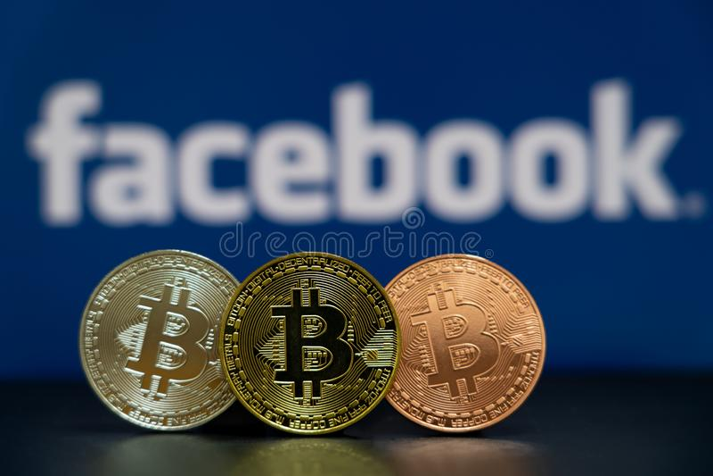 Moeda de Bitcoin com a tela azul do logotipo de Facebook foto de stock royalty free