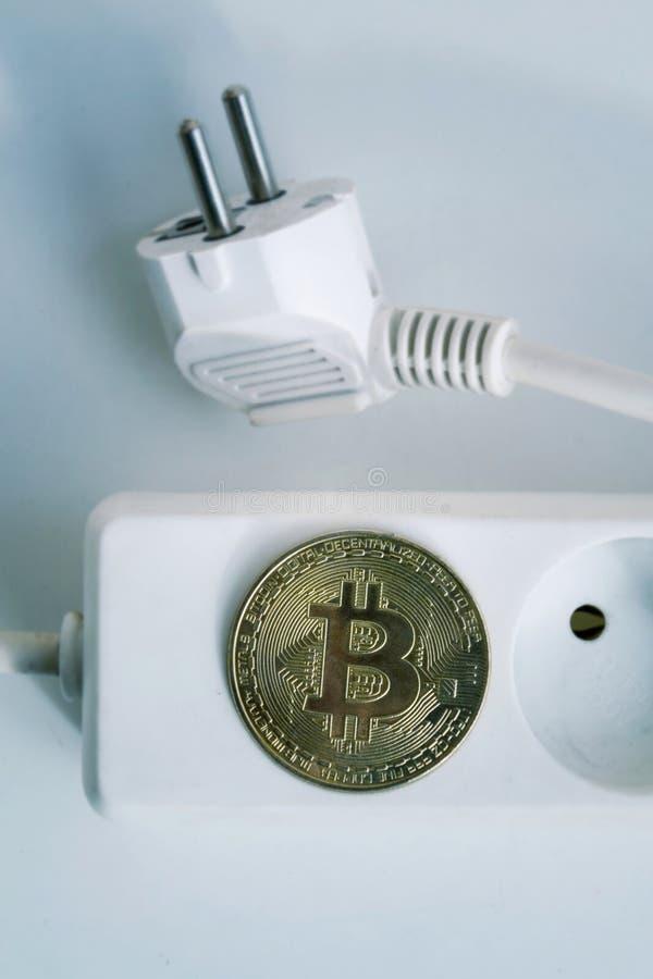 Moeda de Bitcoin que encontra-se no cabo de extensão com os dois soquetes vazios, cryptocurrency da tira do poder que investe, pe foto de stock royalty free
