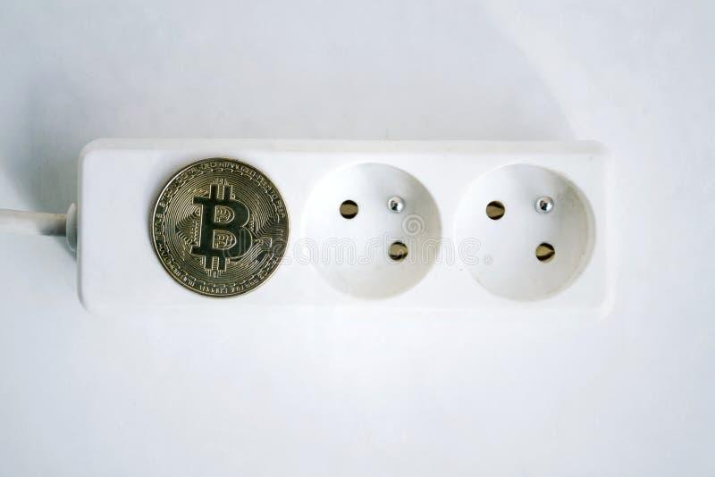 Moeda de Bitcoin que encontra-se no cabo de extensão com os dois soquetes vazios, cryptocurrency da tira do poder que investe, pe imagem de stock royalty free