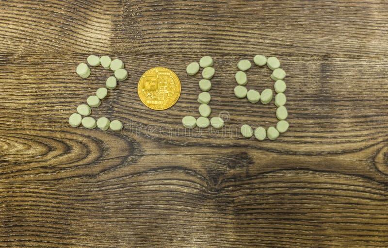 Moeda de Cryptocurrency e texto financeiro do ano do relatório dos doces 2019 na madeira fotos de stock royalty free