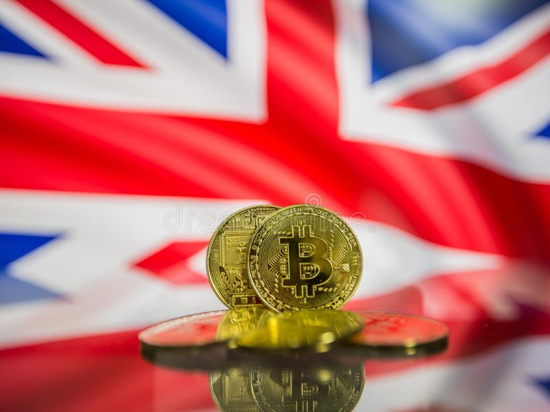 Moeda de ouro de Bitcoin e bandeira defocused do fundo de Reino Unido Conceito virtual do cryptocurrency imagem de stock